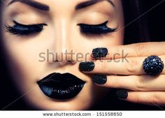 Beauty Fashion Model Girl with Black Make up, Long Lushes. Fashion Trendy Caviar Black Manicure. Nail Art. Dark Lipstick and Nail Polish. Isolated over black background - stock photo