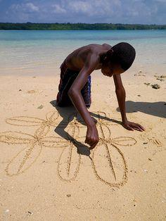 Boy drawing on the sand, Espiritu Santo, Vanuatu. By Eric Lafforgue.