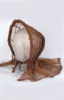 Caned gauze bonnet, c.1845. What a miracle that this rare and delicate bonnet has survived at all! The sheer gauze is more like a whisper than a fabric. And best of all—the bonnet is all original. The frame of the bonnet is fashioned from cane, not metal. The sheer gauze is lined with a stiffer gauze in the back only. The brim and skirt are unlined. The bonnet has its original silk ribbon ties. The outer edge is trimmed with candy-style ribbon self ruffles.