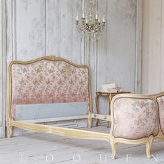 """Beautiful antique Louis XV style bed with a feminine curving frame. In a dusty cream enamel finish, upholstered in worn pink satin damask with brass tacks. Delicate hand-carved floral crest and base carvings in gilt add a romantic touch. Lovely and luxurious find for a master bedroom. Mattress dimensions are approximately 56"""" wide by 72"""" deep.  <br><br> • 45"""" H x 54"""" W x 89""""D<br> • Dusty Cream Enamel Finish<br> • Wood, Satin Damask, Brass Tacks<br> • Circa 1910<br> • This is a one-of-a..."""