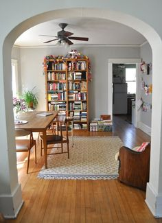 dining room/library- love the kid art display area, the bins of childrens books, the cozy chair in one corner, table by the window with light and plants...