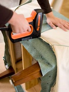 A sleeve of fabric is sewn for the chair seat and pulled on. The back edge of the cover is pulled through the opening between the seat and back and stapled to the frame./