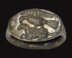 A GREEK BRONZE FINGER RING CLASSICAL PERIOD, CIRCA LATE 5TH CENTURY B.C. With a plain hoop, oval in section, expanding at the shoulders to the oval bezel, engraved with an eagle standing upon a reclining ram, the eagle with its wings raised, its head lowered to the back of the ram's head 7/8 in. (2.2 cm.) wide