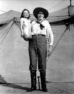 "Mr. and Mrs. Al Tomaini.  In 1949, Tomaini, an 8 ½' tall giant with a 22-inch shoe size retired from the road and settled in Gibsonton, FL.  Al and his two-foot tall wife, Jeanie, billed as ""The Half-Girl,"" adopted two daughters & started a restaurant and trailer park they called ""The Giant's Camp."""