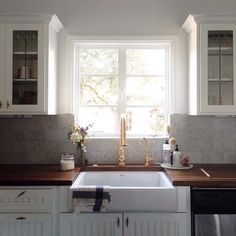 same setup as our kitchen, with the glass cupboards around the window. ideas for farm sink and new countertops.