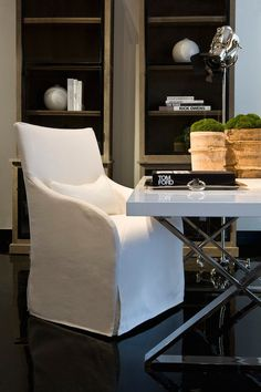 Chic home office with side by side graywash oak bookcases beside a white lacquered desk with x base lined with a swoop arm slipcovered chair over glossy black floors illuminated by a polished nickel spotlight floor lamp.