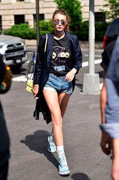 Gigi Haddis usa shorts jeans curto com tenis e blazer mais camiseta estampada