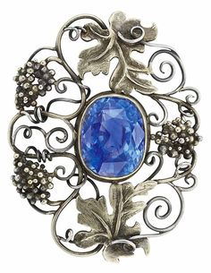 Arts and Crafts Gold, Silver and Colour-Change Sapphire Brooch. Centring one collet-set cushion-cut sapphire approximately 10.75 cts., within an openwork stylised grapevine frame, circa 1900.