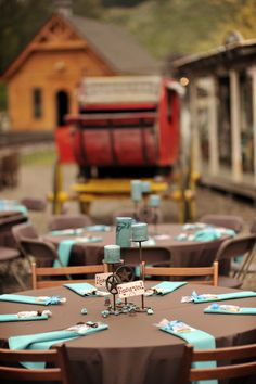 rustic wedding reception tables decorated with chocolate cloths, turquoise napkins, candles, and star iron holders - thereddirtbride.com - see more of this wedding here