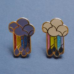 "Art deco influenced cloud, rainbow, and rain design. - Size: 1"" tall x 1mm thickness - Sanded hardened enamel poured into cast metal, smooth to the touch"