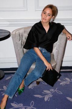 Desi is wearing: Balenciaga Knife mules, Totême Azurro top, Loewe T Pouch, denim jeans, Rhinestones earrings
