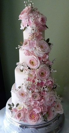 El jardín del país del pastel de bodas blanco y rosas de jardín de azúcar en pasta rosa, ranúnculo rosado, stephanotis blanco, lirio de los valles ramas y hortensias de color rosa pálido caer románticamente por este pastel de boda de cuatro niveles.  Una pieza central elegante para cualquier recepción de la boda, en el país o en la ciudad .: