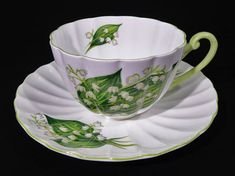 Offering a lovely Shelley Lily of the Valley Ludlow shape Tea Cup and Saucer Duo Lily of the Valley flowers, tiny white bell shape on broad green lily leaves against white ground Green handle and green trim, numbered 13822 Fine Bone China Made in England Circa 1955 ~ 1966 Saucer 5 3/4