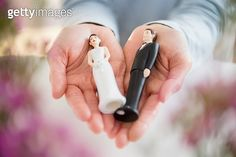Hands holding bride and groom cake toppers - gettyimageskorea