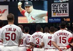 Members of the St. Louis Cardinals watch a video tribute to fallen teammate Darryl Kile during a memorial service before the game against the Milwaukee Brewers Tuesday, June 25, 2002, at Busch Stadium in St. Louis. Kile died Saturday, June 22, in his hotel room in Chicago, apparently due to a heart condition.