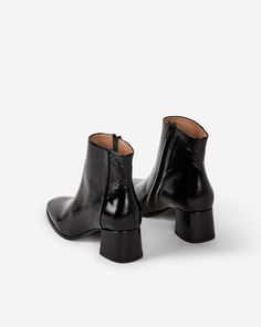 Mid bootie in structured patent leather version and soft goat suede version. Leather sole and 5,5 cm sharp angled heel covered in main material. Long zip on the side. Goat leather lining and insock.