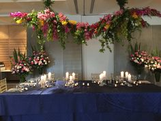 Ceiling Floral Installation Pop of colour pink, orange cymbidiums. Blue Linen and crystal candlesticks federation square Flower Decorations, Wedding Decorations, Table Decorations, Flower Chandelier, Flower Installation, Bridal Table, Sweetheart Table, Floral Wall, Table Linens