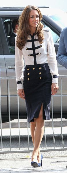 Kate Middleton showed her support of the riot victims with a visit to Summerfield Community Centre. The Duchess of Cambridge opted to wear an Alexander McQueen Pre-Fall 2011 ensemble. Kate selected a silk blouse with navy epaulettes and paired the top with a high-waisted pencil skirt featuring two front slits and matching gold buttons.  Brand: Alexander McQueen