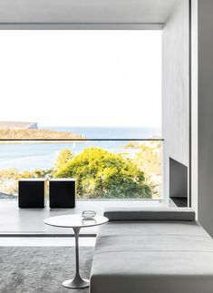 A modern minimalist living room with a balcony that looks out onto the ocean. #livingroom #livingarea #balcony #balconydesign #modernhome #outdoorfireplace Modern Minimalist Living Room, Living Area, Living Rooms, Balcony Design, Coastal Homes, Commercial Interiors, Fashion Room, Neutral Colors, Minimalism