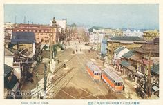 1910's, Tokyo. Looking north-east towards Ginza not too far from the spot where the current Shinbashi subway station is located. Two electrified streetcars, first introduced in 1903 (Meiji 36), are in the front, others can be seen in the far background. The empty space in front of the building with the tower is Shinbashi Bridge.