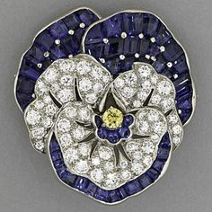 OSCAR HEYMAN SAPPHIRE AND DIAMOND PANSY BROOCH. Retailed by Udall and Ballou, ca. 1935. Mystery-set fancy baguette cut blue sapphires, approx. 6.25 cts. TW with fancy yellow diamond, approx. .16 ct. and 59 full cut near colorless diamond melee, approx. 2.50 cts. TW, in platinum. Stamped Udall & Ballou. 10.60 dwt. (16.48 gs.), 36 mm x 32 mm.