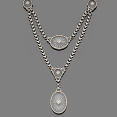 A rock crystal and diamond necklace, attributed to Black Starr & Frost-Gorham, circa 1930  Set to the front with five circular and oval rock crystal reverse-carved plaques, each inset to the centre with a brilliant-cut diamond in a lozenge-shaped collet within an engraved scroll border, connected by swags of finely engraved geometric and palmette-shaped linking, on a single backchain of similar engraved links, to an elliptical engraved clasp, mounted in platinum and yellow gold,