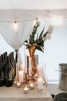 Brass vases and lots of candles - all available for hire with Jade McIntosh flowers