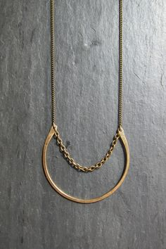 Simple hammered brass loop and antiqued brass finished steel accent chain on a 22 inch antiqued brass chain. Closure is a matching lobster claw clasp. Chain available in 18 or 24 inches upon request. All jewelry is shipped in a brown cardboard jewelry box with cotton padding--ready to be worn or gifted
