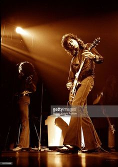 Photo of Jimmy PAGE and LED ZEPPELIN; Robert Plant (background), Jimmy Page (foreground) performing live onstage
