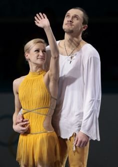 Tatiana Volosozhar and Maxim Trankov of Russia stand on the podium during the flower ceremony following in the pairs free skate figure skati...