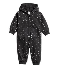 Black/stars. CONSCIOUS. Jumpsuit in soft sweatshirt fabric made from organic cotton with a printed pattern. Jersey-lined hood, zip and pockets at front, and