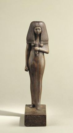 """Statuette of Tuy, Superior of the Harem of the god Min.  The New Kingdom (circa 1550 to circa 1069 BC). The statuette of Tuy is carved from two species of wood that the Egyptians imported from the south - shea wood for the base, and African grenadilla for the lady herself. There are offering formulae on the back pillar and the base, dedicated to Osiris, Isis and """"all the Gods who are in the West (necropolis)"""". 