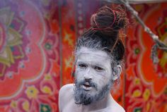 An ash smeared Hindu Sadhu or holy man poses beside a tent in Allahabad