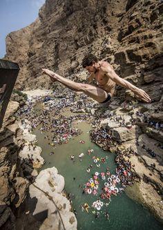 David Colturi, atleta dos EUA, salta de um penhasco a uma altura de 27,5 metros durante a última etapa de competição mundial de salto de penhasco em Wadi Shab, Omã.