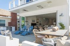 Seaside home features folding glass doors opening to a patio lined with blue loungers next to an x based dining table with a weathered zinc top lined with wicker dining chairs,.