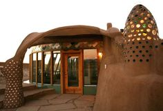 Earthship Homes -- Entry door and windows face southern exposure.  Built with tires, recycled aluminum can, glass bottles and salvaged lumber.  Low impact and zero energy cost by capturing solar power and re-using water.  All the way off the grid!!