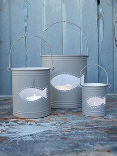 Buckets/tin cans with fish cutouts as lanterns.