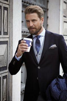 Comprar ropa de este look:  https://lookastic.es/moda-hombre/looks/chaqueta-con-cuello-y-botones-blazer-cardigan-camisa-de-vestir-corbata/9204  — Camisa de Vestir a Cuadros Blanca  — Corbata de Tartán Azul Marino  — Cárdigan Gris  — Blazer Negro  — Chaqueta con Cuello y Botones Acolchada Azul Marino