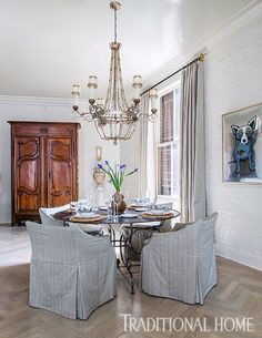 The dining area features slipcovered chairs gathered around a zinc-top table. Shimmer—courtesy of lacquered ceilings, an ornate chandelier, and a mix of metals—infuses glamour. - Photo: Sara Essex Bradley / Design: Chad and Christina Graci