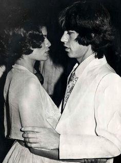 """Bianca Jagger in a fabulous ball at Blenheim Palace appearing with Mick. Bianca was wearing my cream """"torn shell"""" crinoline, complete with a walking stick, looking magnificent! This was featured in Women's Wear Daily.'"""