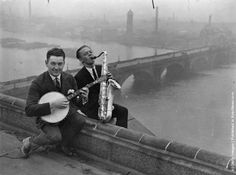A banjo player and saxophonist enjoy an impromptu jam on a roof top in London. (Photo by Topical Press Agency/Getty Images). September 1922