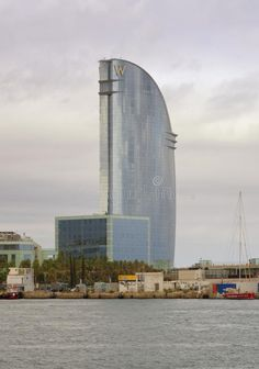 Photo about Barcelona, Spain. People lying on the beach in front of W hotel, also known as Vela or Sail Hotel, barcelona, catalonia, spain. Image of catalunya, european, edifice - 116829282