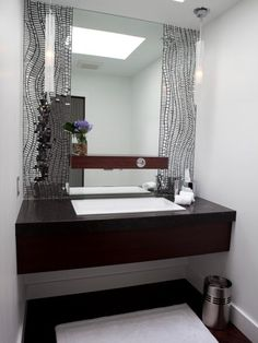 Mirrored mosaic tile frames the main mirror in this contemporary single-vanity bathroom. The beautiful dark vanity appears to float below.