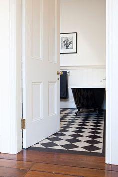 White bead-board; black & white checkered tiles; claw foot bath.