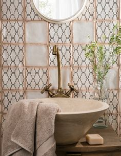 Modernise a distressed tile with a freestanding stone basin and brass fixtures