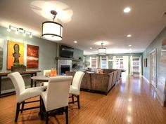 Contemporary furnishings and dual-purpose gathering spaces enhance the look and function of this long, narrow family/game room. With windows fixed at the end of the room, recessed lighting and large pendant fixtures add a sparkling glow of light to the room.