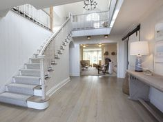 foyer with white wood staircase and oak wood floors Entry Stairs, Entry Foyer, Redo Stairs, Entry Doors, Barn Doors, Sliding Doors, Floor Design, House Design, Bleached Wood