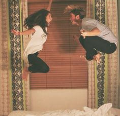 Hotel picture. Couple jumping on bed. Best friends