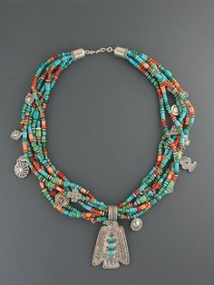Turquoise Treasure Necklace by Don Lucas. Mine is about 30 inches long, is turquoise and coral only, with silver beads and stamped charms of Native American spirit animals and objects, and is finished with a Zuni carved  3-dimensional jadeite bear fetish about 2 inches long with turquoise eyes.