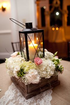 Lantern with hydrangeas, spray roses and babies breath arranged in wooden box.
